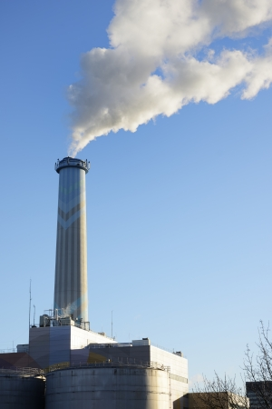 smolder: Heating plant with a high smokestack Stock Photo