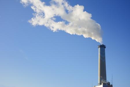smolder: Smoke from a high smokestack Stock Photo