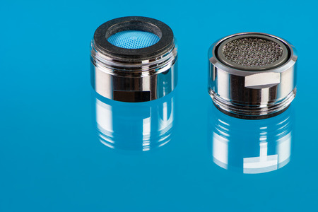 reducing: Macro of two faucet aerators for reducing water consumption.