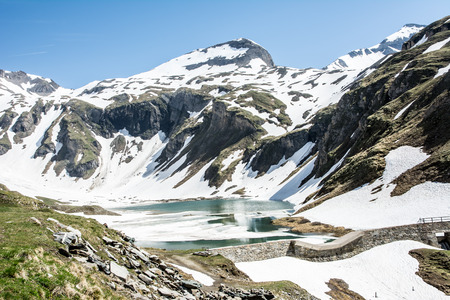 Snowmelt at a half frozen lake in the alps photo