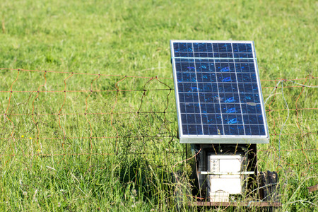 Electric pasture fence charged with a solar panel Stock fotó