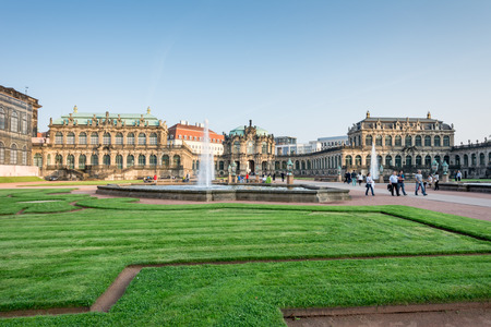 completely: DRESDEN, GERMANY - SEPTEMBER 4: Tourists at the Zwinger palace in Dresden, Germany on September 4, 2014. By 1963 the Zwinger had largely been restored after it was completely destroyed 1945. Foto taken from the public Zwinger park.