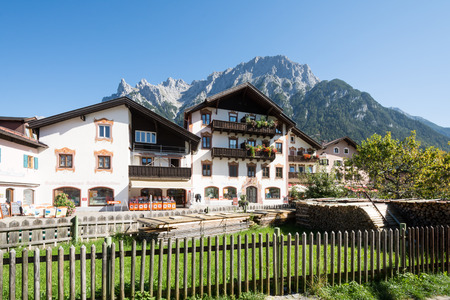 cellos: MITTENWALD, GERMANY - SEPTEMBER 27: Shops in the village of Mittenwald, Germany on September 27, 2014. Mittenwald is famous for the manufacture of violins, violas and cellos. Foto taken from Obermarkt with view to the Karwendel Mountains. Editorial