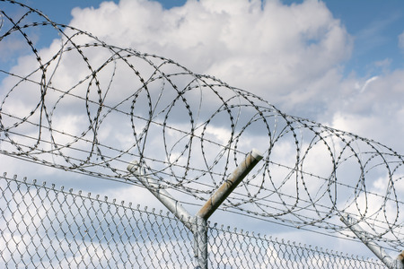 jailhouse: Security barrier with a barbed wire fence