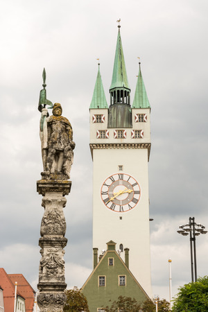 Historic tower (called Stadtturm) of Straubing and a sculpture of the Tiburitiusbrunnen from 1685.