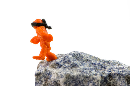 abyss: Self-made human plasticine figure walking to the edge of the abyss. Stock Photo
