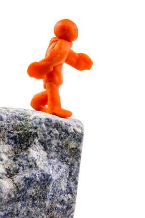 Self-made human plasticine figure walking to the edge of the abyss. Stock Photo