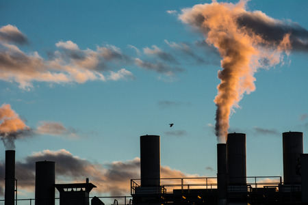 Air pollution from smokestacks of a factory in the sunset.