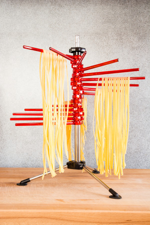selfmade: Self-made italian tagliatelle hanging on a pasta drying rack.