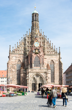 hauptmarkt: NUERNBERG, GERMANY - APRIL 9: Tourist at the Frauenkirche in Nuernberg, Germany on April 9, 2015. The church is a brick gothic architecture built in the 14th century. Foto taken from Hauptmarkt.