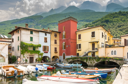 frequented: CASSONE, ITALY - JUNE 1: Marina in Lake Garda at Cassone, Italy on June 1, 2015. Lake Garda is one of the most frequented tourist regions of Italy. Foto taken from the port with view to the village. Editorial