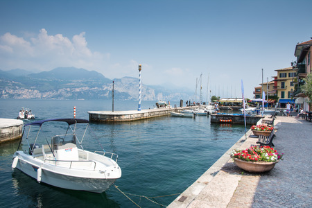 frequented: CASTELLETTO, ITALY - JUNE 2: Marina at Lake Garda in Castelletto, Italy on June 2, 2015. Lake Garda is one of the most frequented tourist regions of Italy. Foto taken from Castelletto water front with view to the marina. Editorial