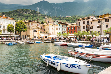 frequented: MALCESINE, ITALY - JUNE 1: Marina at Lake Garda in Malcesine, Italy on June 1, 2015. Lake Garda is one of the most frequented tourist regions of Italy. Foto taken from piazza Guglielmo Marconi with view to the port.