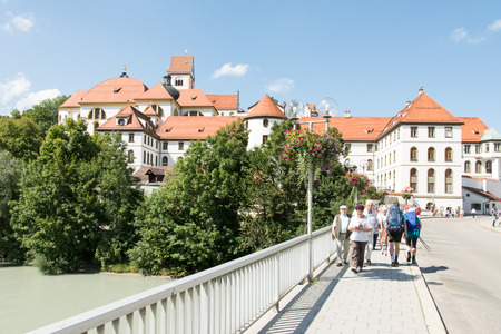 mang: FUESSEN, GERMANY - AUGUST 22: Tourists at the Kloster Sankt Mang in Fuessen, Germany on August 22, 2015. The abbey was founded in the 9th century. Foto taken from Lechhalde with view to the abbey.
