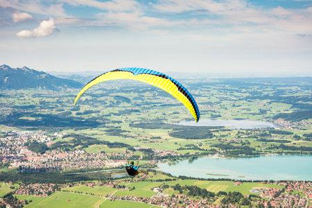 schwangau: SCHWANGAU, GERMANY - AUGUST 23: Unknown paraglider on mount Tegelberg in Schwangau, Germany on August 23, 2015. Tegelberg is one of the most popular paragliding areas in Germany. Foto taken from Tegelberg. Editorial