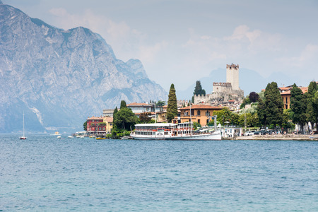 frequented: MALCESINE, ITALY - JUNE 1: Lake Garda water front at the village Malcesine, Italy on June 1, 2015. Lake Garda is one of the most frequented tourist regions of Italy. Foto taken from south of the town with view to the village.