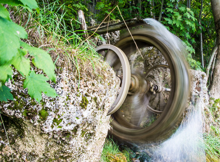 blurred motion: Blurred motion of a vintage spinning water wheel Stock Photo