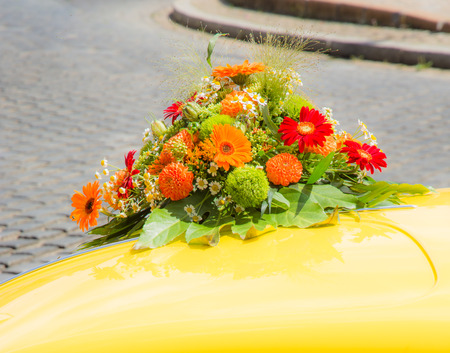 old timer: Bridal bouquet on a yellow wedding old timer car