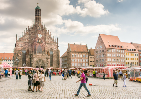 hauptmarkt: NUERNBERG, GERMANY - SEPTEMBER 5: Tourist at the Frauenkirche in Nuernberg, Germany on September 5, 2015. The church is a brick gothic architecture built in the 14th century. Foto taken from Hauptmarkt.