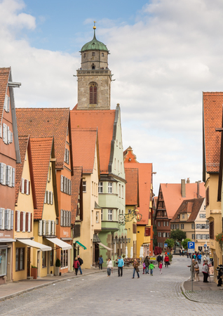 minster: DINKELSBUEHL, GERMANY - SEPTEMBER 27: Tourists in the old town of Dinkelsbuehl, Germany on September 27, 2015. It is one of the best preserved medieaval towns in Germany. Foto taken from Segringer street with view to the minster St. Georg.