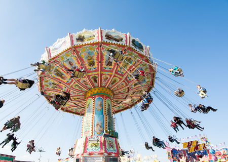 MUNICH, GERMANY - SEPTEMBER 30: People in a chairoplane on the Oktoberfest in Munich, Germany on September 30, 2015. The Oktoberfest is the biggest beer festival of the world with over 6 million visitors each year. Foto taken from Theresienwiese. Editorial