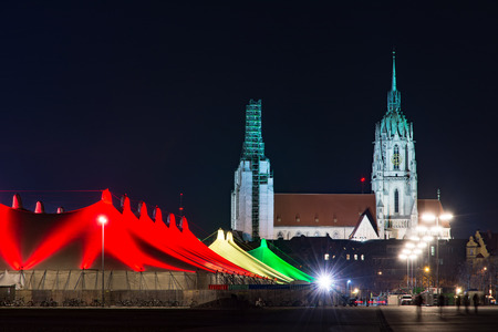 christkindlmarkt: MUNICH, GERMANY - DECEMBER 12: Illuminated tents at the Tollwood winter festival in Munich, Germany on December 12, 2015.  Foto taken from Theresienwiese with view to the festival tents and St. Paul Church.