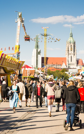 MUNICH, GERMANY - SEPTEMBER 30: Visitors of the Oktoberfest in Munich, Germany on September 30, 2015. The Oktoberfest is the biggest beer festival of the world with over 6 million visitors each year. Foto taken from Theresienwiese.