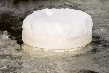 Floating ice preventer made of styrofoam in a frozen pond