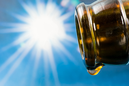 refractions: Last drop of an empty beer bottle with the sun in the background
