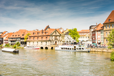 passenger ship: BAMBERG, GERMANY - MAI 6: Tourists on a passenger ship at river Regnitz in Bamberg, Germany on Mai 6, 2016. Foto taken from Untere  Bruecke with view to Am Kranen.