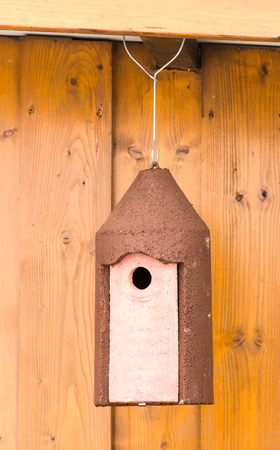 loophole: Closeup of a birdhouse  hanging at a wooden hut
