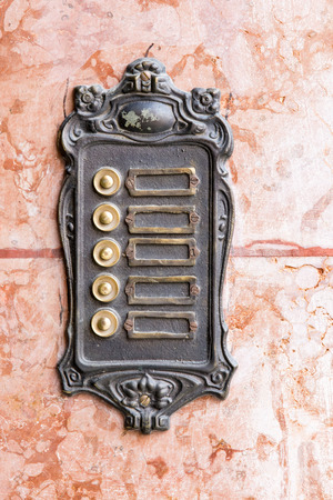 rustiness: Old vintage rusty doorbells on a marble wall