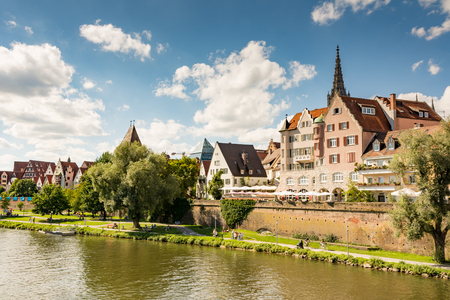 ULM, GERMANY - AUGUST 13: People walking along the Danube river in Ulm, Germany on August 13, 2016. Ulm has the highest spire of the world. Foto taken from Donaustrasse. Editorial