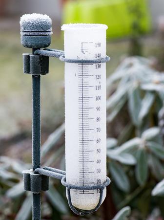 rain gauge: Meteorología con un pluviómetro en el jardín - congelado después de una noche fría