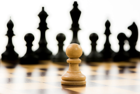White pawn against a superiority of black chess pieces on a chess board. Selective focus.