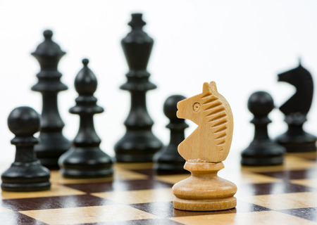 strategical: White knight against a superiority of black chess pieces on a chess board. Selective focus.