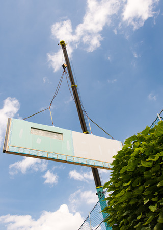 Assembling a prefabricated house - wall is hanging on a crane