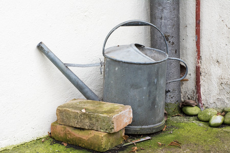 Vintage watering can at a house wall