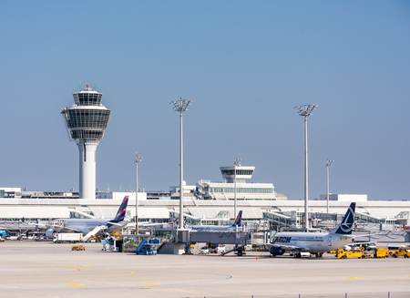 MUNICH, GERMANY - APRIL 9: Planes in parking position at the the airport of Munich, Germany on April 9, 2017. The ariport has over 40 million passengers a year. Foto taken from the visitor platform of the airport. Stock Photo - 77803406