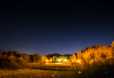 Illuminated campground at night with a starry sky