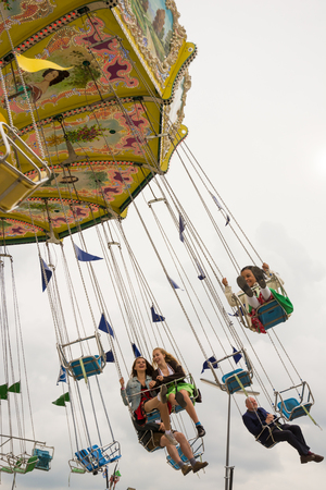 MUNICH, GERMANY - SEPTEMBER 19: People in a chairoplane on the Oktoberfest in Munich, Germany on September 19, 2017. The Oktoberfest is the biggest beer festival of the world with over 6 million visitors each year.
