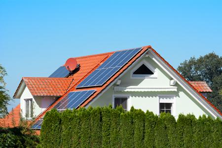 Casa moderna con células solares fotovoltaicas en el techo para producción de energía alternativa