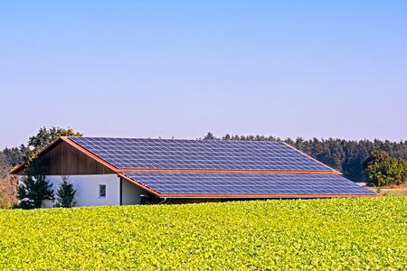 Zielona energia z kolektorami słonecznymi na dachu budynku rolniczego
