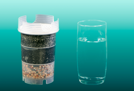 Water purification filter with active carbon and a glass of fresh and clean drinkable water 版權商用圖片 - 116246563