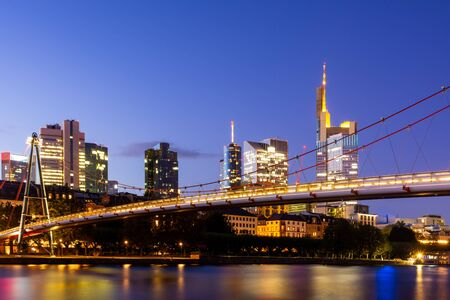 The Holbeinsteg footbridge in Frankfurt acrross Main river with view to the skyline at night