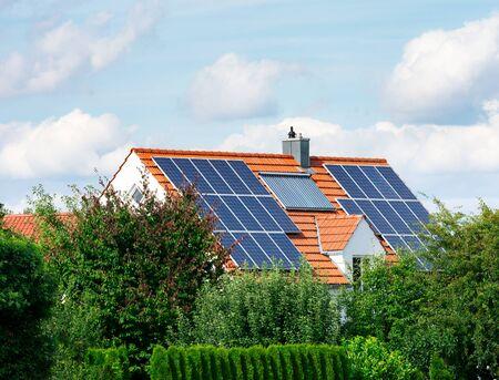 Nowoczesny dom z fotowoltaicznymi ogniwami słonecznymi na dachu i termicznym systemem ogrzewania słonecznego do alternatywnej produkcji energii