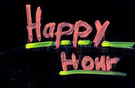 Happy hour written in pink on black chalkboard with chalk