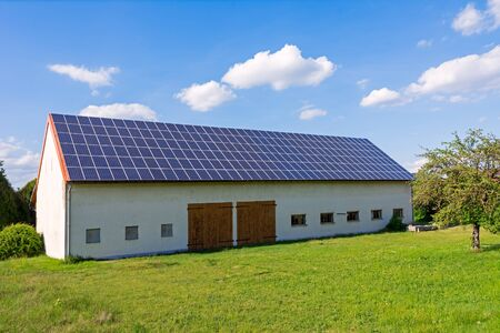 Green energy with solar collectors on the roof of an agricultural building