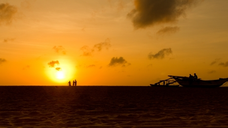 Family fun on a beach with sunset and boat in the background photo
