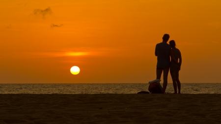 Loving couple enjoying sunset on a sandy beach photo